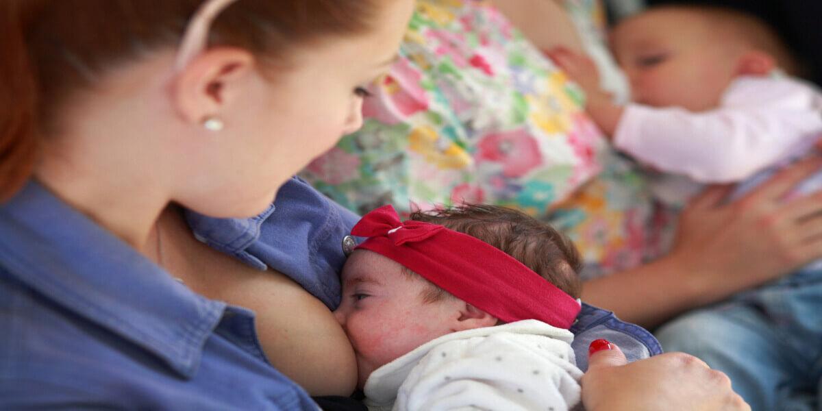 Otrok, ki se doji pri svoji materi na srečanju za spodbujanje dojenja.